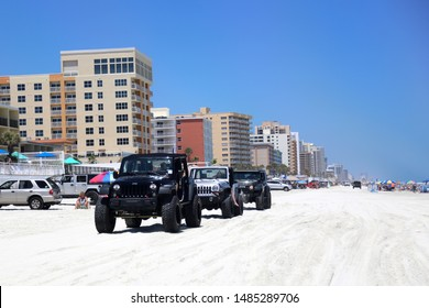 Daytona Beach, Florida / USA - May 1 2019: Multi-colored jeep wranglers ride on Daytona Beach