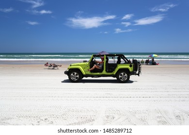 Daytona Beach, Florida / USA - May 1 2019: Multi-colored jeep wranglers ride on Daytona Beach
