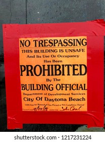 """DAYTONA BEACH, FLORIDA-MAY 27, 2018:  Actual """"No Trespassing"""" sign hanging on an abandoned business.  The sign indicates the building is unsafe."""