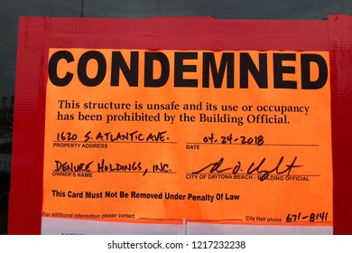 """DAYTONA BEACH, FLORIDA-MAY 27, 2018:  Actual """"Condemned"""" sign hanging on an abandoned business along with a demolition order."""