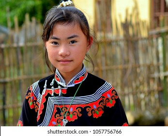 DAYUTANG, YUNNAN/CHINA - NOV 15, 2012: Pre-teen Miao girl (Chinese ethnic minority) wears a colorful traditional ethnic costume and poses for the camera at her parents' farm, on Nov 15, 2012.