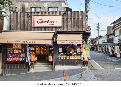 Dazaifu, Japan - November 19, 2018: Local shops and stores sell souvenirs and local snacks along the street near Dazaifu Tenmangu Shrine entrance, Japan