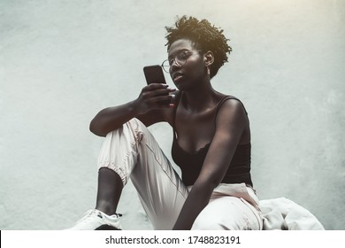 A dazzling authentic African girl in spectacles and with a nail-art using smartphone while sitting in front of a white wall; a charming young black woman in eyeglasses sending a message via cellphone