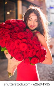 Dazzling lady stands and keeps big bouquet of red roses in hands, looks at it, on the street