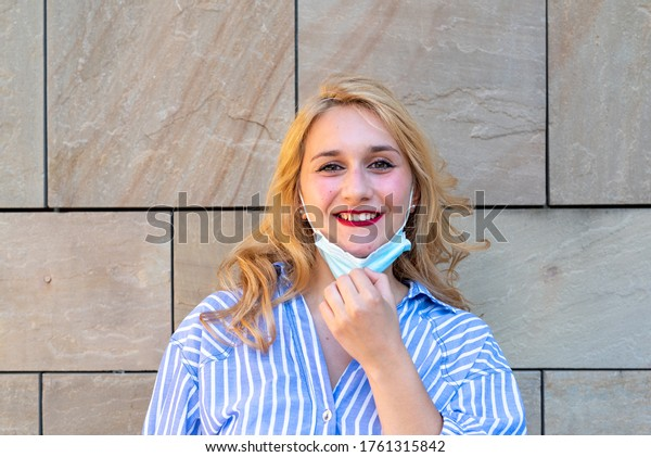the dazzling smile of a young millennial girl who lowers her protective mask, a concept of optimism and positivity during the period of a world pandemic