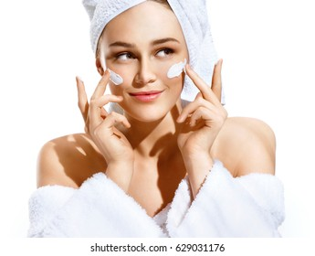 Dazzling young woman applying moisturizing cream on her face. Photo of woman in white bathrobe and towel on white background. Skin care concept