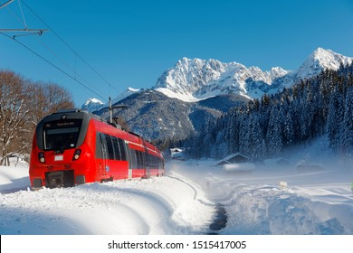 A DB train travels thru a forest in a valley covered by heavy snow & Karwendel mountain stands under clear sky in background on a sunny winter day near Klais & Garmisch-Partenkirchen, Bavaria, Germany