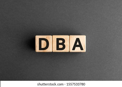 DBA - acronym from wooden blocks with letters, DataBase Administrator or doing business as abbreviation DBA concept, gray background