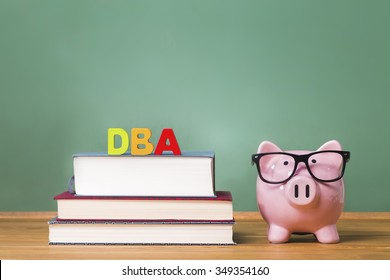 DBA theme with pink piggy bank with chalkboard in the background as concept image of the costs of education