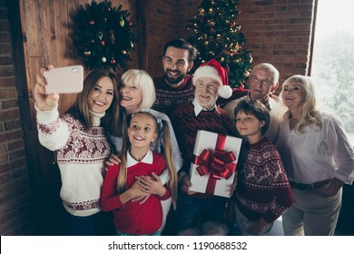 Dcember 2019 tradition x-mas. Portrait of cheerful full family noel gathering. Grey-haired grandparents, grandchildren, sister, brother, son, daughter taking self photo on cell mobile phone fun joy