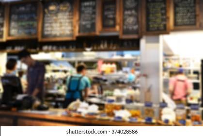 De focused/ Blurred image of restaurant staff busy in preparing meal.
