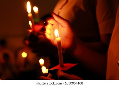 De focused Candlelight with people. Bokeh of light candle,Crowds gather to do candlelight activities. Closeup of people holding candle vigil in darkness expressing and seeking hope.