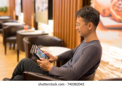De focused senior smart man with eyeglasses  smiling looking  at  tablet  in cafe restaurant. Blurred middle aged male in cafe.