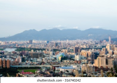 De focused/Blurred image of a city surrounded by mountains from high point. A river winding through city. City and mountain background.