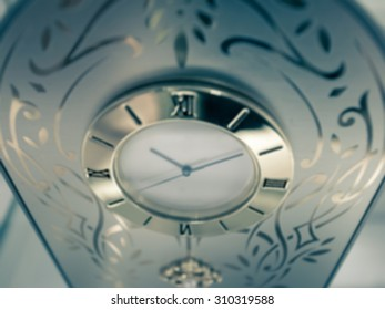De focused/Blurred image of a clock with indicator hands pointing at 10:10.  Shot from above. Split tone.