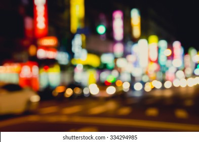 De focused/Blurred image of night city. Vehicles on the road. Shop signs with red, yellow, blue, brown colors.