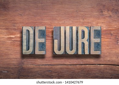 de jure ancient Latin saying meaning «something established by law» combined on vintage varnished wooden surface