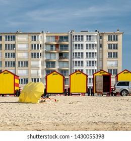 De Panne, Belgium - 18 April 2019: beach parasols and vintage beach huts.