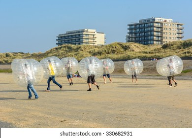 De Panne, Belgium 3 October 2015: Playing bubble bump soccer on the beach