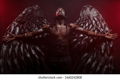 dead african guy became an angel with big magnificent wings, dark angel fallen from heaven. african shirtless man stand with spreading hands and looking up. interesting people, afterworld, fancy