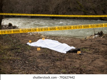 Dead body and evidence markers with crime scene tracks all around them.
