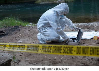 Dead body, forensic in white and crime scene track in foreground.