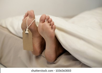 Dead body laying on the floor showing only feet. Grungy photo of feet with toe tag on a morgue table.