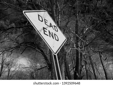 Dead end sign with creepy trees and ominous storm clouds in black and white