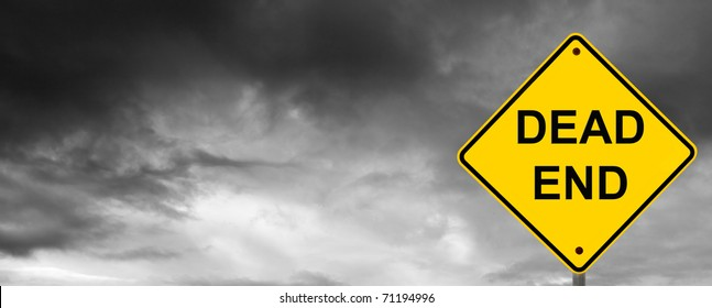 Dead end sign with dark storm clouds behind.
