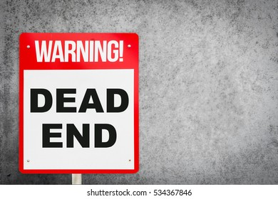 Dead End warning sign with gray cement wall.