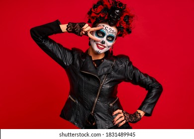 Dead gir with sugar skull makeup with a wreath of flowers on her head and skull, wearth lace gloves and showing victory sign isolated on red background.Concept of Halloween or La Calavera Catrina.