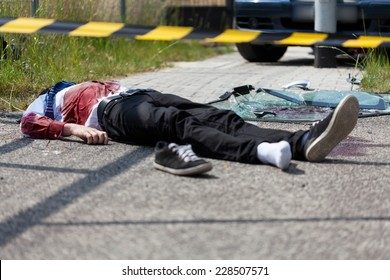 A dead man lying on the road after a car crash