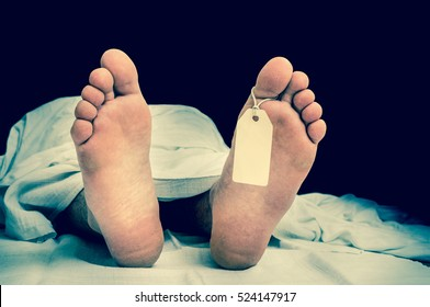 The dead man's body with blank tag on feet under white cloth in a morgue - retro style