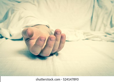 The dead man's body under white cloth with focus on hand in a morgue - retro style