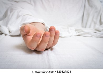 The dead man's body under white cloth with focus on hand in a morgue