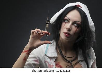 Dead nurse holding syringe with blood