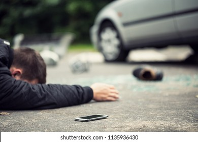 Dead pedestrian lying on the street next to his phone. Shoe, broken glass and car blurred in the background
