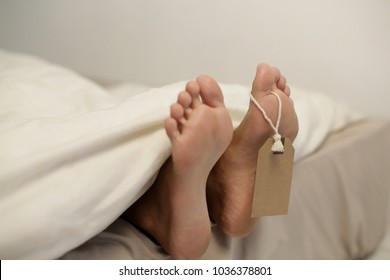 Dead person body lying in the morgue. Grungy photo of feet with toe tag on a morgue table.