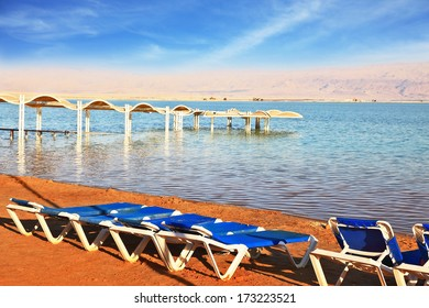 The Dead Sea, the blue beach chairs waiting for tourists. Beautiful sunny day at a beach resort