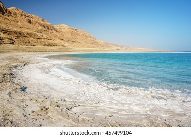 Dead Sea coastline with white salt beach and mountains at sunny day in Ein Bokek, Israel. Famous Middle East health landmark. White mineral salt beach at Dead sea, Israel. Dead sea landscape of Israel
