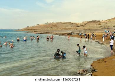 DEAD SEA, JORDAN -MARCH 05: Unidentified people enjoy a swim in the salt lake, unsinkable for heavy salinity and mud used for medical treatment, March 05, 2019 in Dead Sea, Jordan