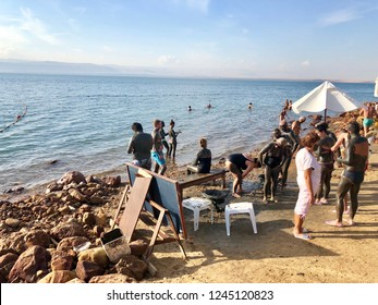 DEAD SEA, JORDAN - NOVEMBER 20, 2018: People floating on very salty water and applying mineral mud to their skin at a hotel beach on the Dead Sea, Jordan.