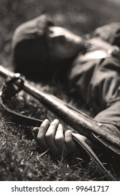 Dead soldier lying on the ground with a gun in his hand
