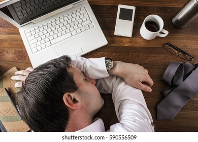 dead tired business man taking break sleeping on desk at work