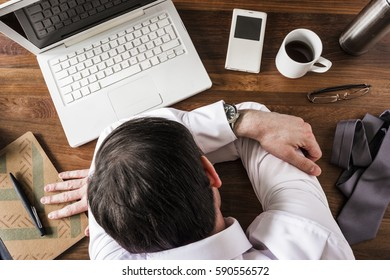 dead tired business man taking break sleeping on desk at work
