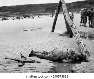 Dead U.S. soldier on Omaha beach on D-Day, June 6, 1944. Crossed rifles in the sand are a comrade's tribute. He was killed during the Normandy landings in Nazi occupied France, World War 2.