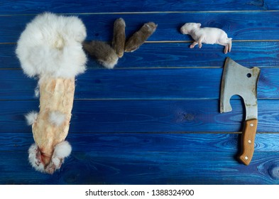 A dead white rabbit and a rabbit skin on a blue Board with an ax and the pieces of rabbit