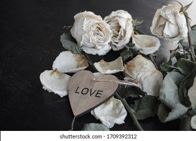 dead withered crumbling flowers roses with a wooden heart with the inscription love, as a symbol of failed love, goodbye, broken hearts, the end of relationships, divorce