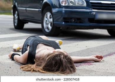 A dead woman in blood after a car accident