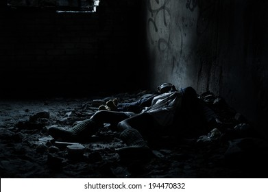 Dead woman lying on the dirty floor in a heap of rubbish in the basement